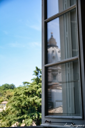 Reflection of the tower in a window and the view on Vatican Garden